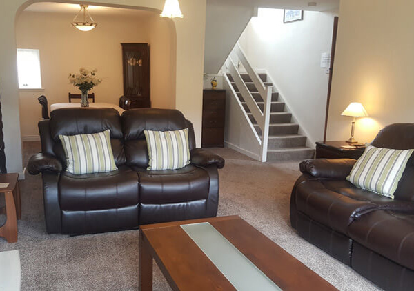 Cosy and Traditionally Furnished Lounge Area with Brown Leather Sofas and Small Coffee Table in Cheviot Holiday Cottage