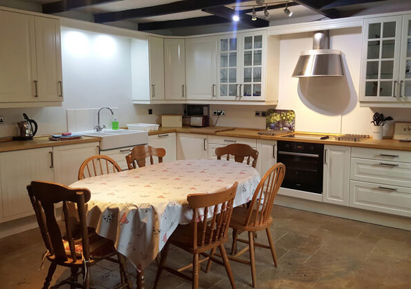 6-seated wooden dining room table inside a traditional refurbished kitchen with exposed stone walls and floors