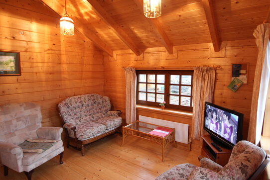 Warm and comfortable open-plan living area with Scandinavian style design in Pine Lodge, Luxury Log Cabin